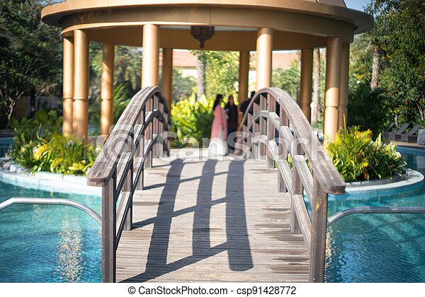 locked shot of arched wooden bridge with swimming pool on both sides with blue water and out of focus people in the distance moving and enjoying the vacation in this resort - csp91428772