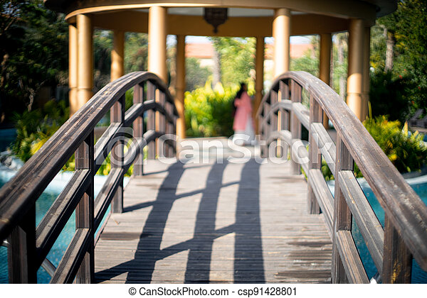 locked shot of arched wooden bridge with swimming pool on both sides with blue water and out of focus people in the distance moving and enjoying the vacation in this resort - csp91428801