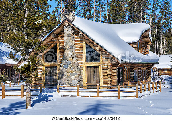 log cabin in the winter forest of idaho log cabin and fence with a