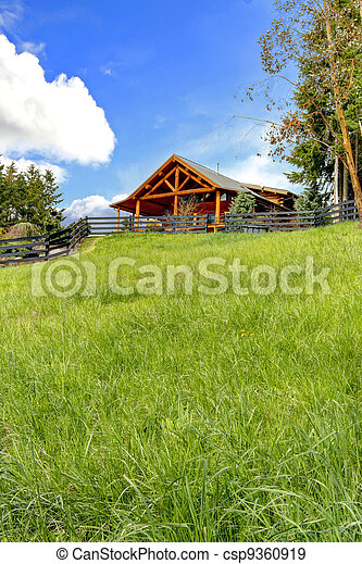 Log cabin on the hill with fresh green grass. - csp9360919