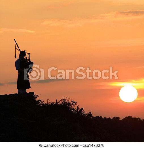 Lone bagpiper at sunset - csp1476078