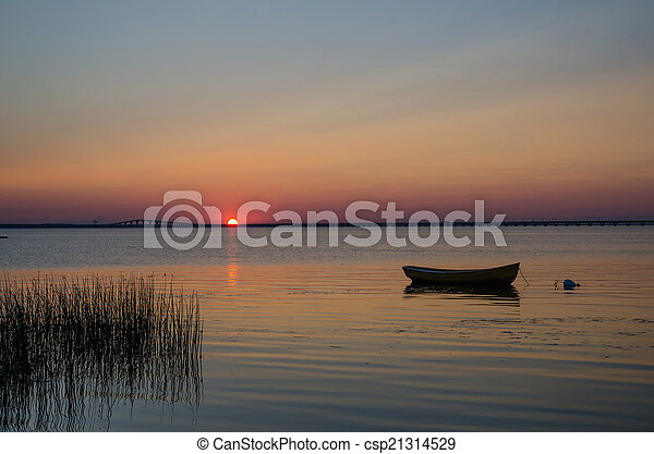 Lone rowboat in calm water at sunset - csp21314529