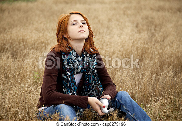 Lonely sad red-haired girl at field - csp8273196