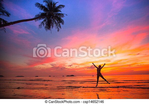 Una joven en un salto en la playa del mar al atardecer - csp14652146