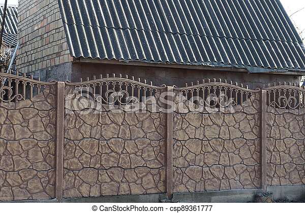 long brown stone wall of a fence on the street - csp89361777