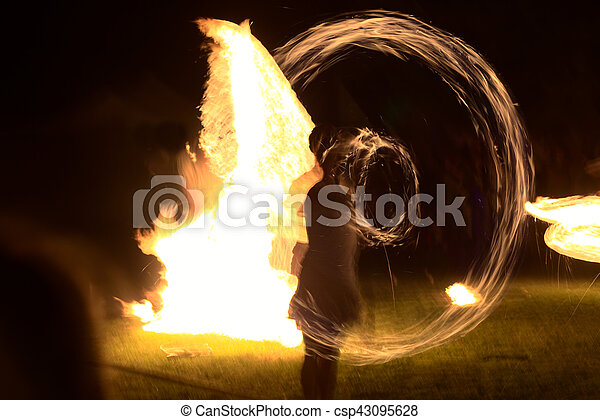 Long exposure shot of moving burning torches and fire with vague silhouette of a person - csp43095628