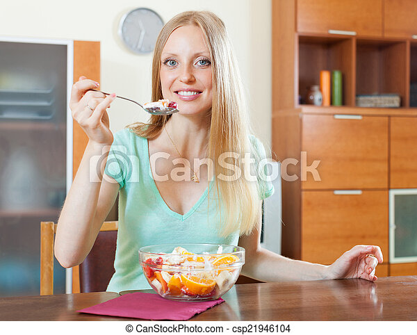 long-haired blonde girl eating fruit salad in home - csp21946104