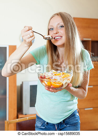 long-haired blonde girl eating fruit salad in home - csp15689035