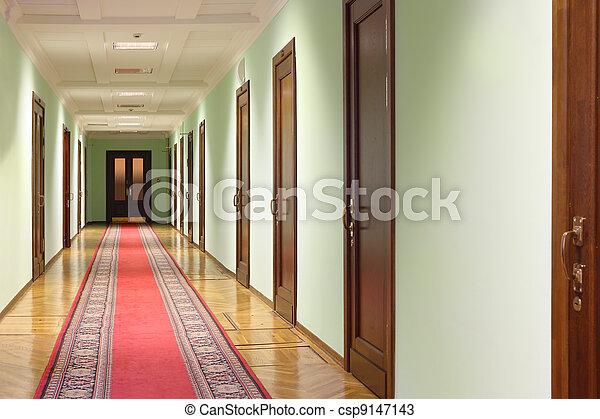 long hallway with brown wood doors, door at end of corridor, red carpet on floor - csp9147143