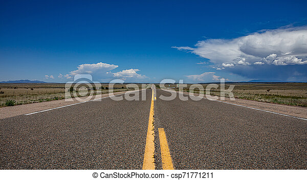 Long highway in the american desert, blue sky with clouds - csp71771211