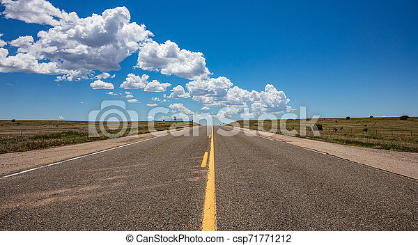 Long highway in the american desert, blue sky with clouds - csp71771212