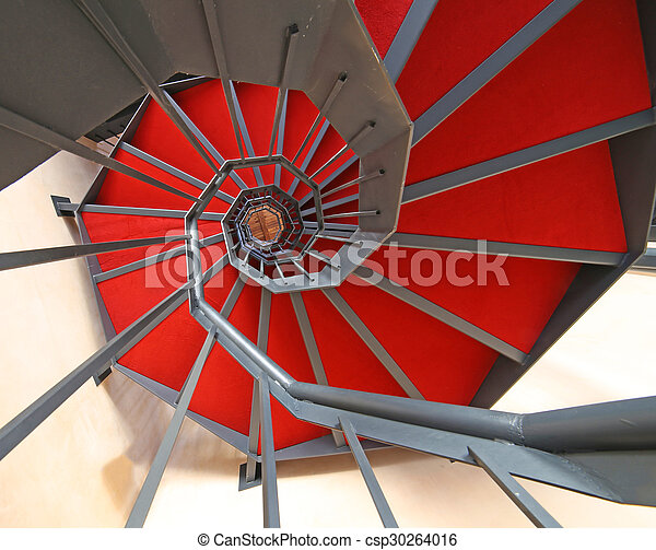long spiral staircase with red carpet in a building - csp30264016