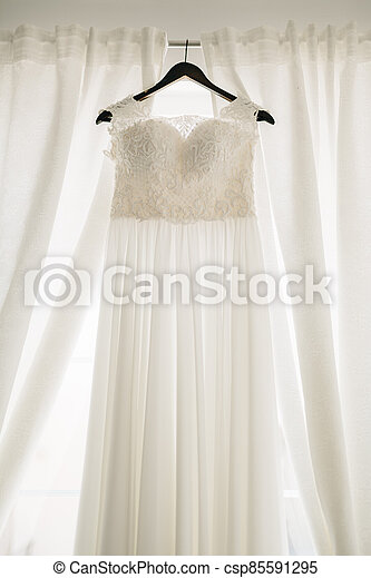 Long white dress of the bride with a lace corset on a black hanger against a background of white curtains. - csp85591295