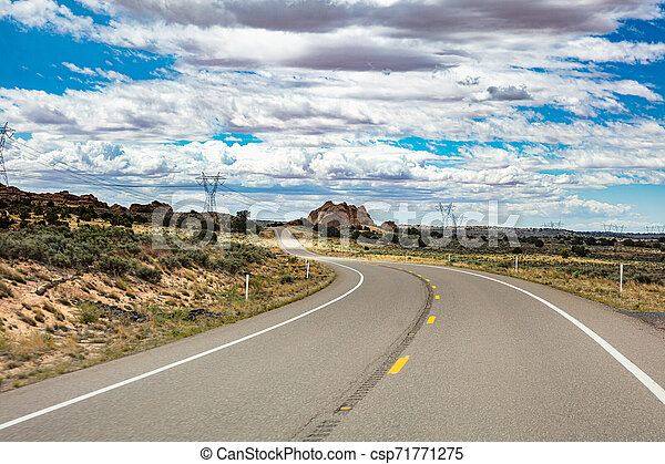 Long winding highway in the american countryside, blue sky with clouds - csp71771275