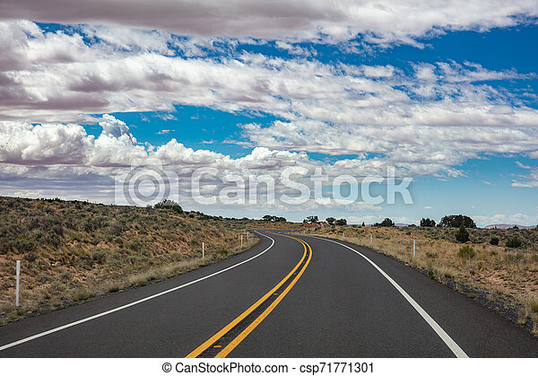 Long winding highway in the american countryside, blue sky with clouds - csp71771301