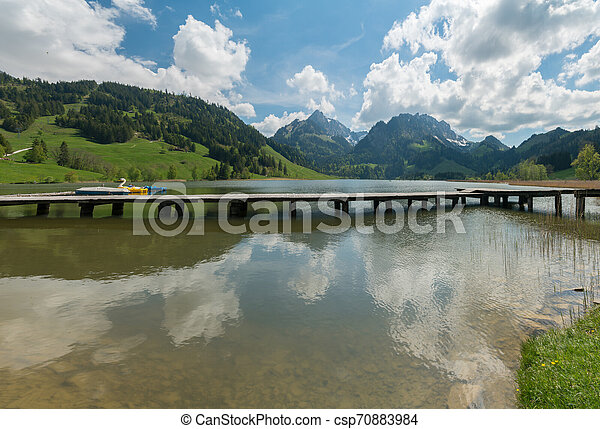 long wooden boardwalk on a calm and placid mountain lake with a great view - csp70883984