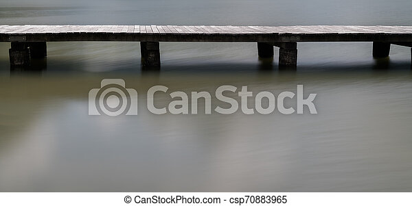 long wooden boardwalk on a calm and placid mountain lake abstract view with copy space - csp70883965