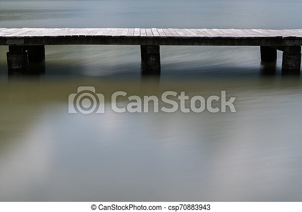 long wooden boardwalk on a calm and placid mountain lake abstract view with copy space - csp70883943