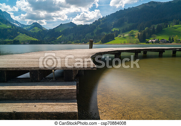 long wooden boardwalk on a calm and placid mountain lake with a great view - csp70884008