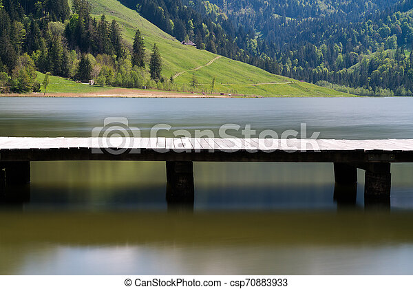 long wooden boardwalk on a calm and placid mountain lake with a great view - csp70883933