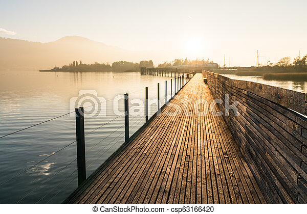 long wooden boardwalk pier over water in golden evening light with a mountain landscape silhouette in the background - csp63166420