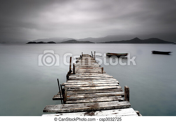 Looking over a desolate pier and a boat - csp3032725