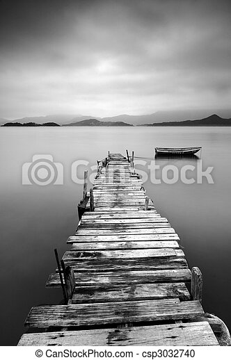 Looking over a desolate pier and a boat, black and white - csp3032740