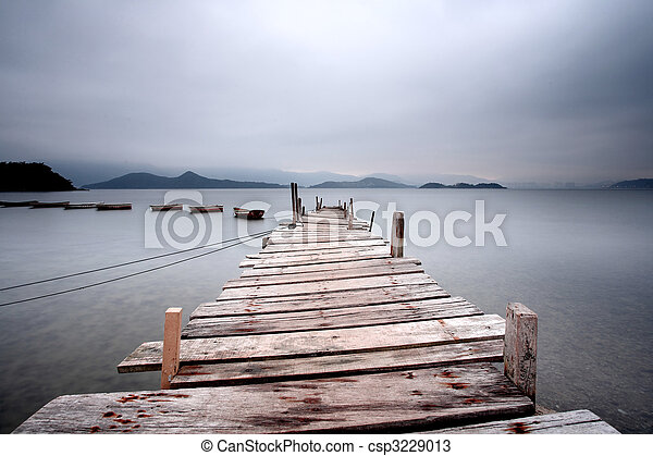Looking over a pier and a boat, dark tone - csp3229013