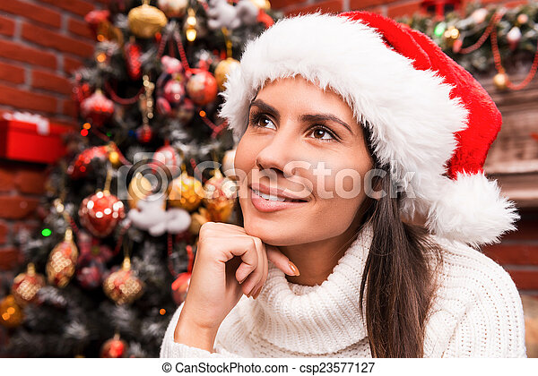 Lost in Christmas thoughts. Thoughtful young woman in Santa hat holding hand on chin and looking away while sitting in front of the Christmas Tree  - csp23577127