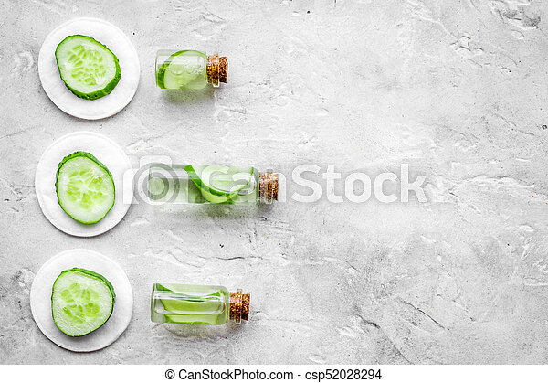 Lotion with cucumber pattern. Grey background top view copyspace - csp52028294