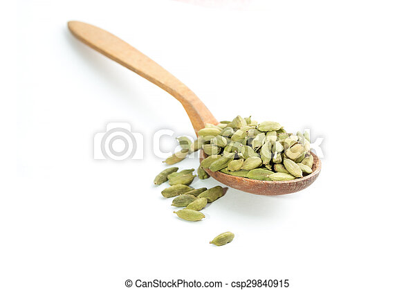 Lots of cardamom pods on wooden spoon isolated on white background - csp29840915