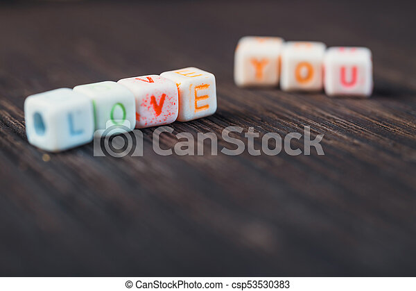 Love message written in wooden blocks on wooden background - csp53530383