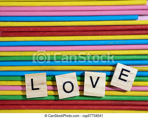 Love message written in wooden blocks placed on colourful wood sticks - csp57734541