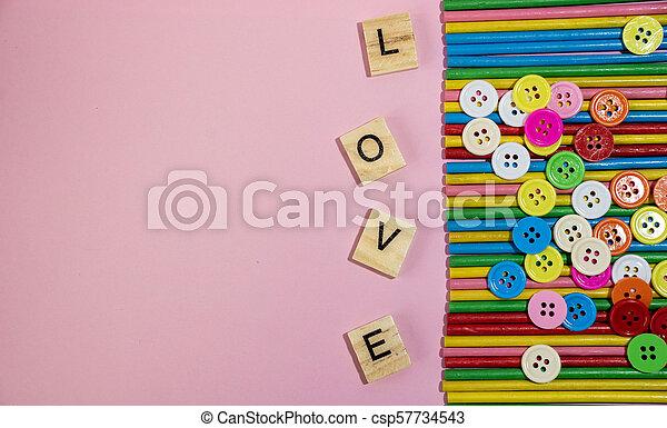 Love message written in wooden blocks placed on pink background - csp57734543
