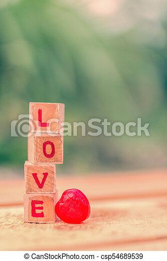 Love message written in wooden blocks. - csp54689539