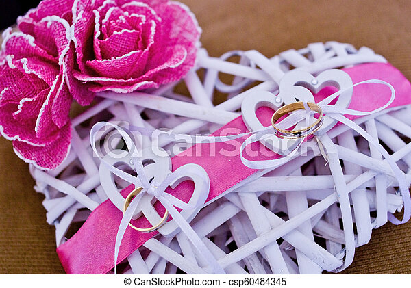 love rings of the newlyweds on heart decorated with pink bow - csp60484345