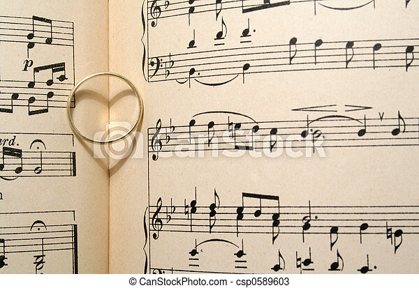Love song Golden wedding ring on old sheet music casting a