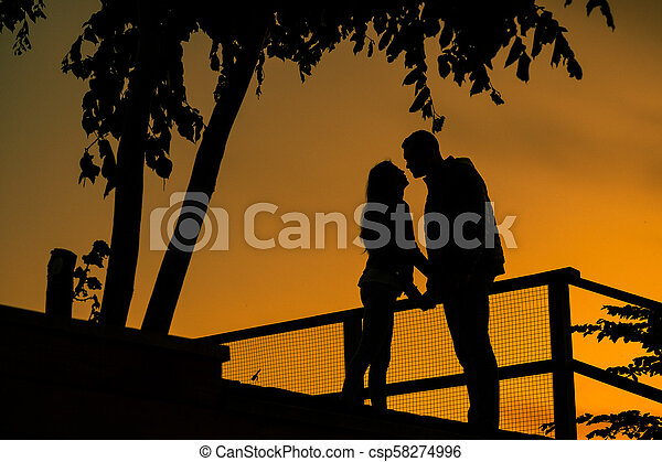 Love story. Couple on the sunset. Silhouette of Lovers - csp58274996