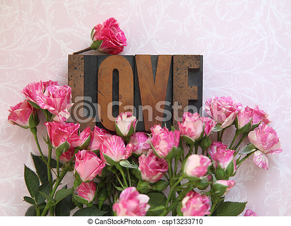 love word in wood type with roses - csp13233710