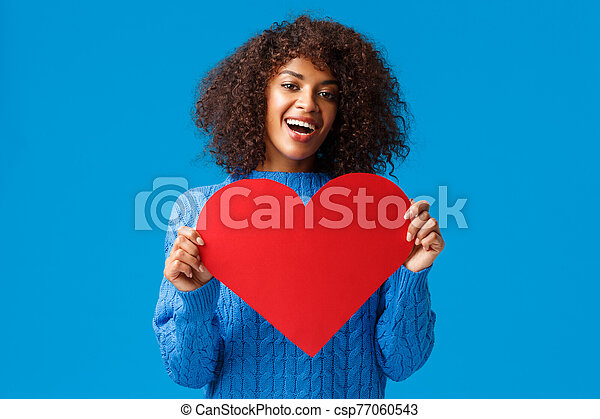 Lovely and cute african-american pretty woman with afro haircut, holding valentines day card, big heart and smiling, express love and affection, showing true feelings, search soulmate - csp77060543