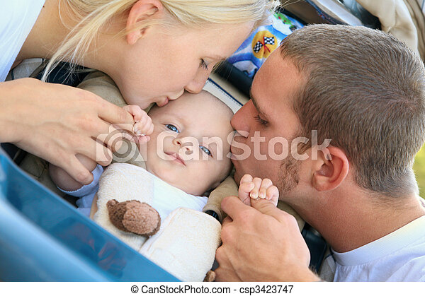 Lovely Caucasian Parents Kiss Their Baby Son - csp3423747