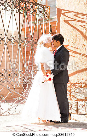 Lovely couple in love kissing each other on the day of a wedding - csp33618740