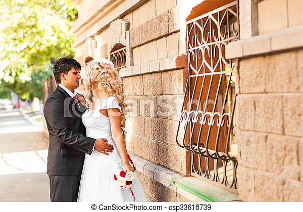 Lovely couple in love kissing each other on the day of a wedding - csp33618739
