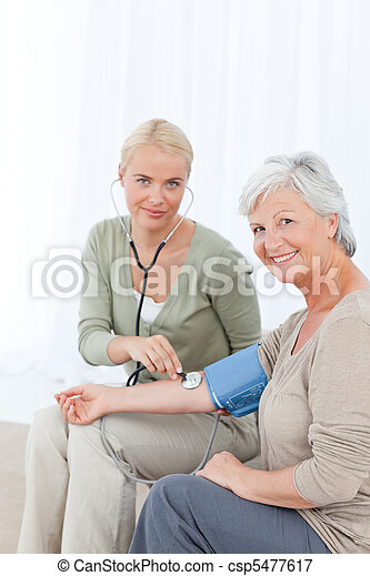 Lovely doctor taking the blood pressure of her patient - csp5477617