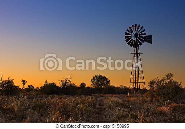 Lovely sunset in Kalahari with windmill and grass - csp15150995