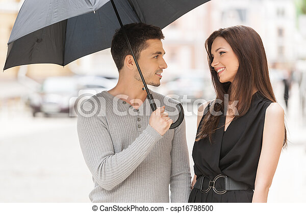 Loving couple. Cheerful young couple standing close to each other while man holding umbrella - csp16798500
