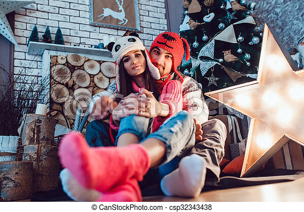 Loving Couple In Funny Hats Posing Christmas Decorations
