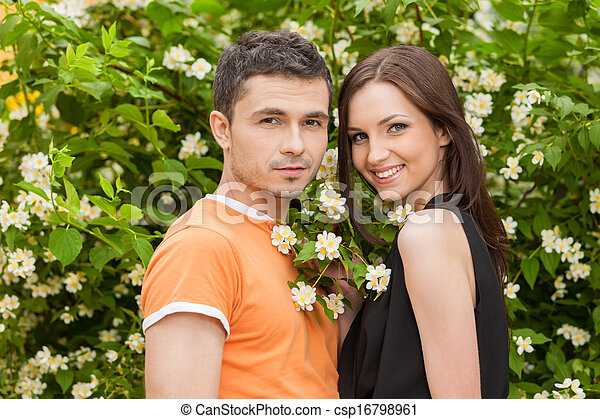 Loving couple in park. Cheerful young couple standing close to each other and looking at camera - csp16798961