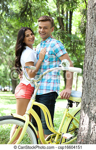 Loving couple with bike. Cheerful young loving couple standing close to each other and leaning at the bike - csp16604151