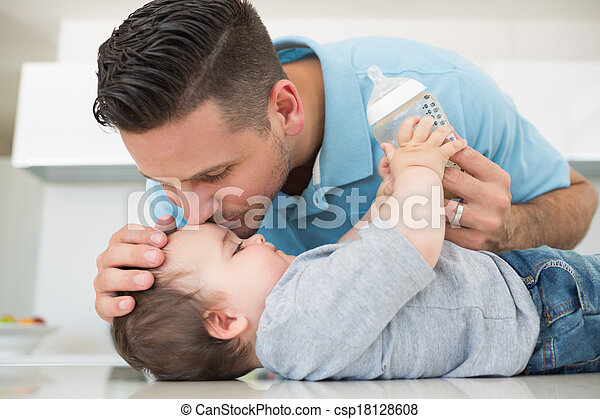 Loving father kissing baby boy on f - csp18128608